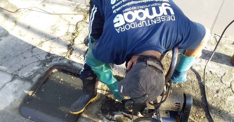 Profissional da Ymaa desentupindo a rede de esgoto residencial