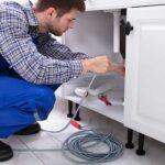 Profissional da desentupidora realiza manutenção na tubulação do condomínio